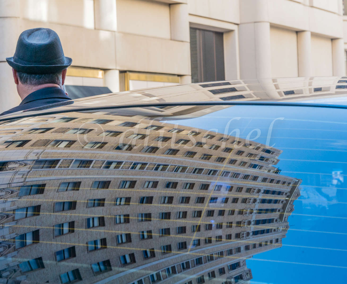 A limousine driver, in a black hat, stands facing away whose head and neck are visible because he is blocked by the rear window of his limo. The window reflects the high-rise buildings on Powell St. in San Francisco.