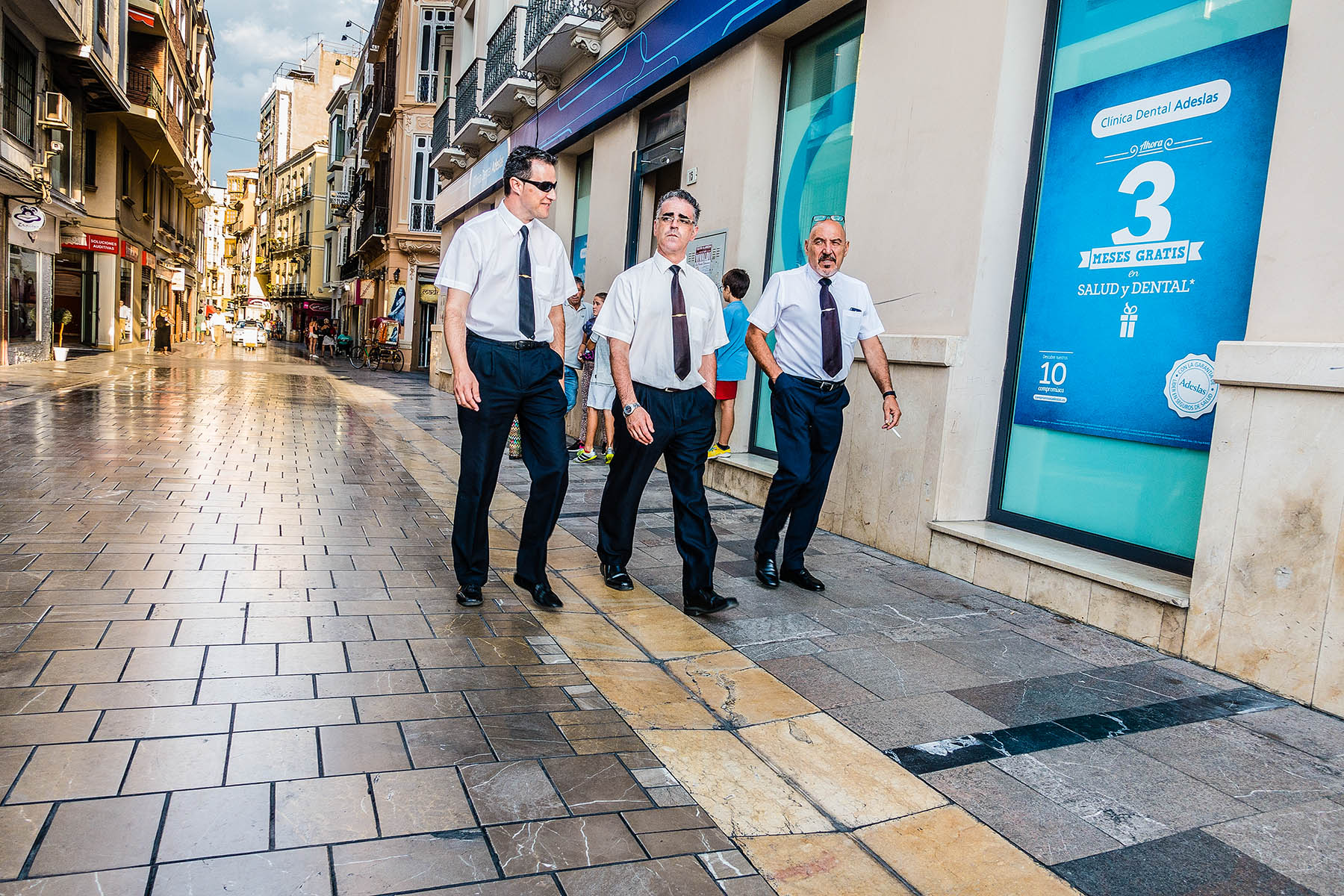 Three businessmen dressed identically alike, with white shirt, black tie, black slacks, black shoes and similar tie clasps walk in the streets of Málaga, Spain.