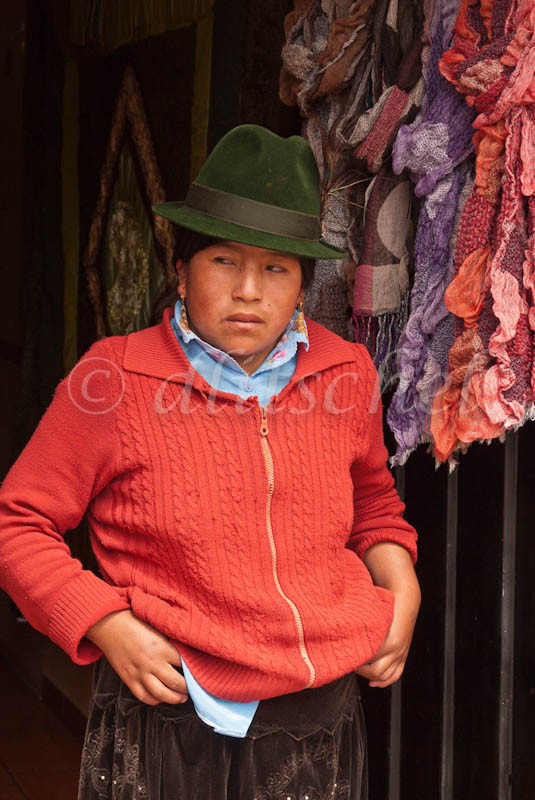 An indigenous female store owner stands in the doorway of her store across from the central market in Octovalo, Ecuador. She is dressed traditional clothing including a {quote}fedora{quote} type hat, worn by women of the region. She is looking to the side.
