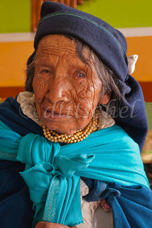 A elderly indian woman faces forward showing head and shoulders with heavily wrinkled face, poor eyesight and traditional clothing in Octovalo, Ecuador.