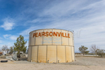 A large water tank at the semi ghost town of Pearsonville, California that has painted on it {quote}Hub Cap Capital of the World{quote} due to the collection of 80,000 hubcaps by Lucy Pearson.