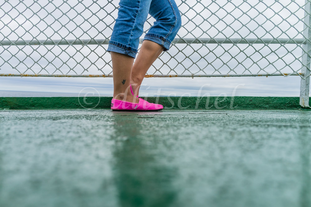 A girl in jeans and hot pink shoes stands by the ship's railing while traveling on the ferry between Prince Edward Island and Nova Scotia, Canada.
