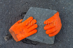 Two brilliant orange worker's gloves rest on paving stone in Peggys Cove, Nova Scotia, Canada.
