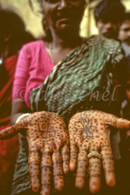 Indian woman with henna dye on her hands depicting ancient Hindu symbols including the swastika, in the southern Indian city of Chennai, formerly known as Madras. To purchase this image, please go to my stock agency click here.
