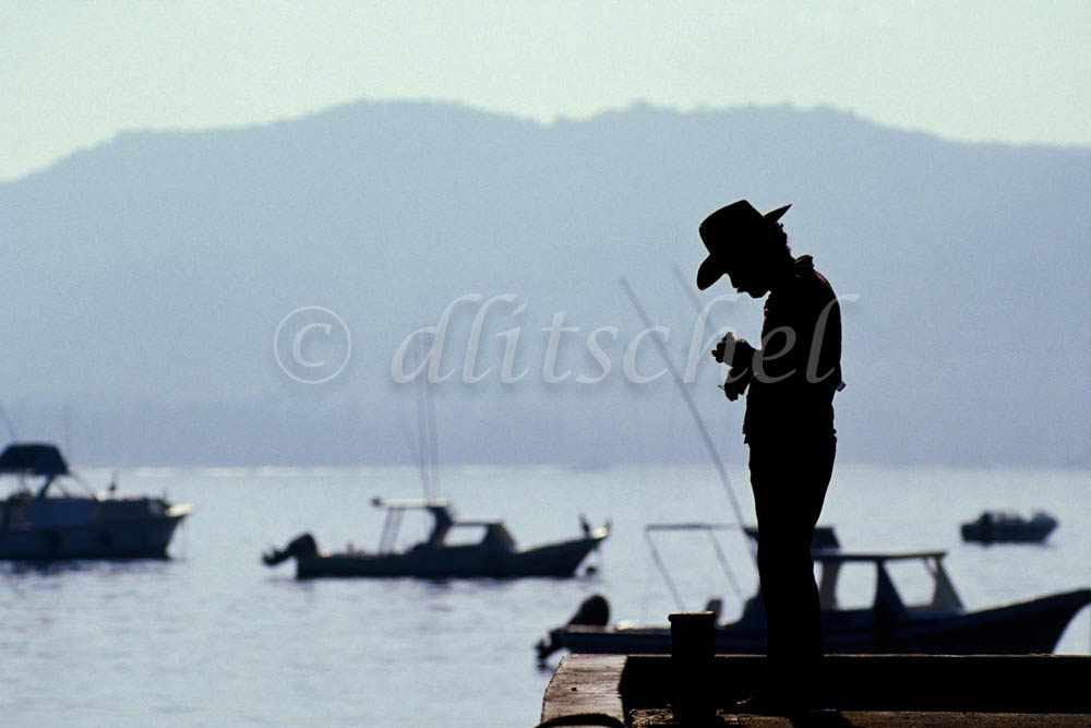 Silhouette of a man fishing at harbor of Zihuantanejo, Mexico. To purchase this image, please go to my stock agency click here.