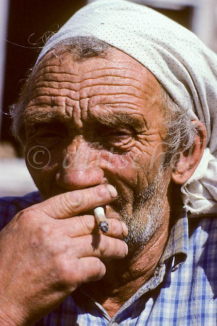 Siberian  adult male wearing headscarf with cigarette, Krasnoyarsk Krai region of Siberia. To purchase this image, please go to my stock agency click here.