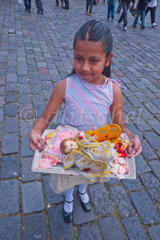 A young Hispanic girl, aged 9-10, carrying a doll on the day of the children when residents of Quito, Ecuador bring dolls to their church.