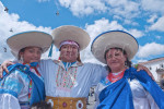 Three Hispanic dancers, two women and a man, from a folklorico group in Quito, Ecuador pose after performing a traditional dance in the San Francisco Plaza. All three are wearing sombreros and customary clothing.