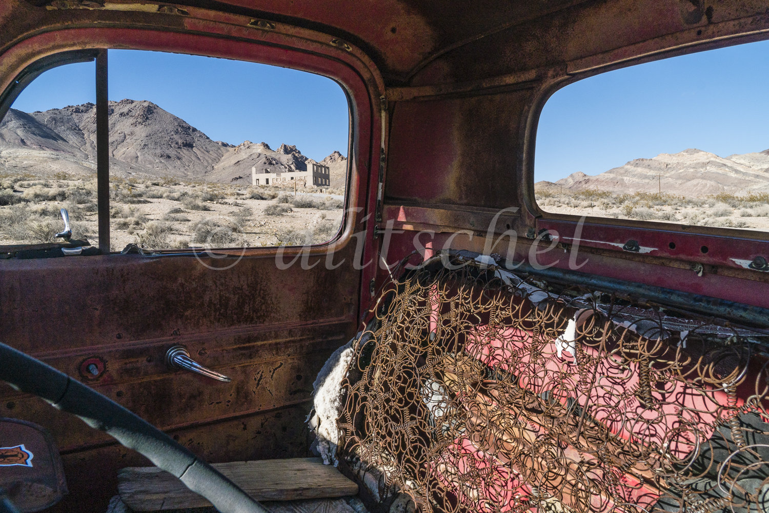 Looking through the window of an abandoned wrecked old red truck in the foreground and the ruins of a building in the ghost town of Rhyolite, Nevada in the background against the surrounding mountains. Rhyolite is a ghost town in Nye County, in the U.S. state of Nevada. It is in the Bullfrog Hills, about 120 miles (190 km) northwest of Las Vegas, near the eastern edge of Death Valley. The town began in early 1905 as one of several mining camps that sprang up after a prospecting discovery in the surrounding hills. During an ensuing gold rush, thousands of gold-seekers, developers, miners and service providers flocked to the Bullfrog Mining District. Many settled in Rhyolite, which lay in a sheltered desert basin near the region's biggest producer, the Montgomery Shoshone Mine.Industrialist Charles M. Schwab bought the Montgomery Shoshone Mine in 1906 and invested heavily in infrastructure, including piped water, electric lines and railroad transportation, that served the town as well as the mine. By 1907, Rhyolite had electric lights, water mains, telephones, newspapers, a hospital, a school, an opera house, and a stock exchange. Published estimates of the town's peak population vary widely, but scholarly sources generally place it in a range between 3,500 and 5,000 in 1907–08.Rhyolite declined almost as rapidly as it rose. After the richest ore was exhausted, production fell. The 1906 San Francisco earthquake and the financial panic of 1907 made it more difficult to raise development capital. In 1908, investors in the Montgomery Shoshone Mine, concerned that it was overvalued, ordered an independent study. When the study's findings proved unfavorable, the company's stock value crashed, further restricting funding. By the end of 1910, the mine was operating at a loss, and it closed in 1911. By this time, many out-of-work miners had moved elsewhere, and Rhyolite's population dropped well below 1,000. By 1920, it was close to zero.After 1920, Rhyolite and its ruins bec