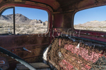 Looking through the window of an abandoned wrecked old red truck in the foreground and the ruins of a building in the ghost town of Rhyolite, Nevada in the background against the surrounding mountains. Rhyolite is a ghost town in Nye County, in the U.S. state of Nevada. It is in the Bullfrog Hills, about 120 miles (190 km) northwest of Las Vegas, near the eastern edge of Death Valley. The town began in early 1905 as one of several mining camps that sprang up after a prospecting discovery in the surrounding hills. During an ensuing gold rush, thousands of gold-seekers, developers, miners and service providers flocked to the Bullfrog Mining District. Many settled in Rhyolite, which lay in a sheltered desert basin near the region's biggest producer, the Montgomery Shoshone Mine.Industrialist Charles M. Schwab bought the Montgomery Shoshone Mine in 1906 and invested heavily in infrastructure, including piped water, electric lines and railroad transportation, that served the town as well as the mine. By 1907, Rhyolite had electric lights, water mains, telephones, newspapers, a hospital, a school, an opera house, and a stock exchange. Published estimates of the town's peak population vary widely, but scholarly sources generally place it in a range between 3,500 and 5,000 in 1907–08.Rhyolite declined almost as rapidly as it rose. After the richest ore was exhausted, production fell. The 1906 San Francisco earthquake and the financial panic of 1907 made it more difficult to raise development capital. In 1908, investors in the Montgomery Shoshone Mine, concerned that it was overvalued, ordered an independent study. When the study's findings proved unfavorable, the company's stock value crashed, further restricting funding. By the end of 1910, the mine was operating at a loss, and it closed in 1911. By this time, many out-of-work miners had moved elsewhere, and Rhyolite's population dropped well below 1,000. By 1920, it was close to zero.After 1920, Rhyolite and its ruins became a tourist attraction and a setting for motion pictures. Most of its buildings crumbled, were salvaged for building materials, or were moved to nearby Beatty or other towns, although the railway depot and a house made chiefly of empty bottles were repaired and preserved. From 1988 to 1998, three companies operated a profitable open-pit mine at the base of Ladd Mountain, about 1-mile (1.6 km) south of Rhyolite.