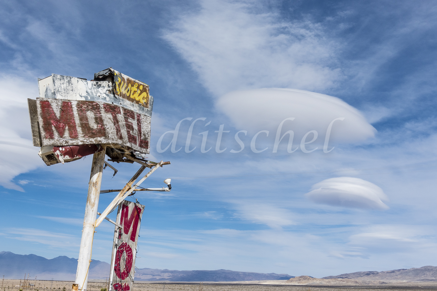 The Rustic Oasis Motel sign with a lenticular cloud formation behind it. The Rustic Oasis Motel is an American roadside attraction along California highway 395 in the Eastern Sierra. Lenticular clouds (Altocumulus lenticularis in Latin) are stationary clouds that form in the troposphere, typically in perpendicular alignment to the wind direction. They are often comparable in appearance to a lens or saucer. Because of their unique appearance, they have been brought forward as an explanation for some unidentified flying object UFO sightings.
