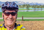 Self portrait of photographer David Litschel in his bicycle helmet with a lake, palm trees and mountains in the background.