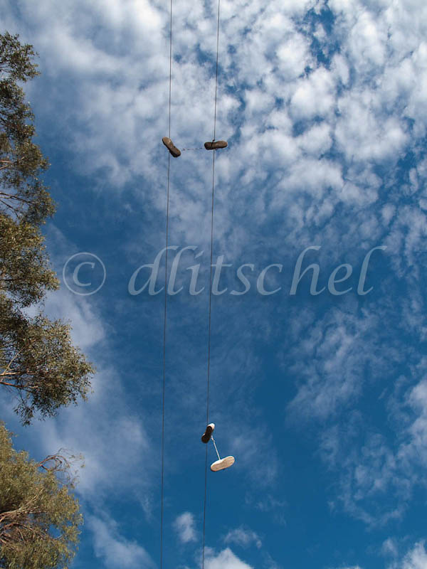Two pairs of shoes hang by their laces from a power line in Santa Barbara, CA.