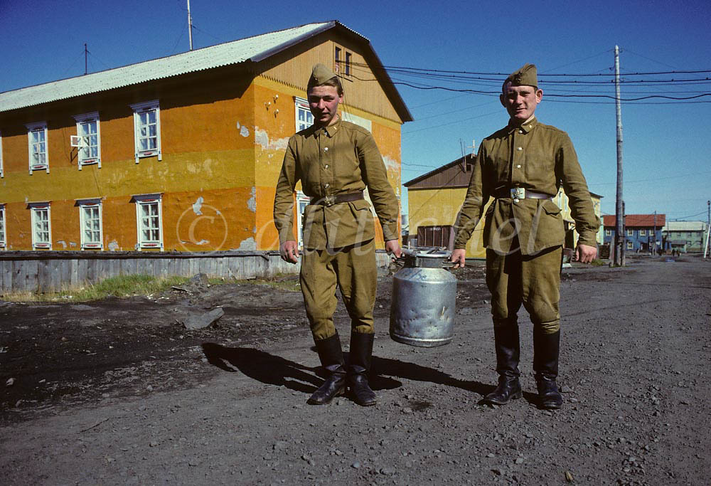 Two Russian soldiers stationed in the far north Arctic town of Dikson, located at the far northern extremes of the Krasnoyarsk Krai, on the Kara Sea, carry a metal container of milk outside their barracks. To purchase this image, please go to my stock agency click here.
