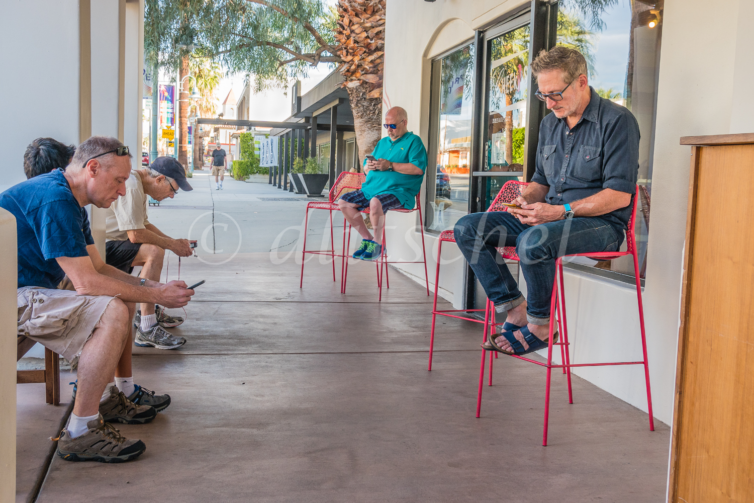 Adult males sitting, waiting for a table and focusing on their smartphones as entertainment outside a restaurant in Palm Springs, California.