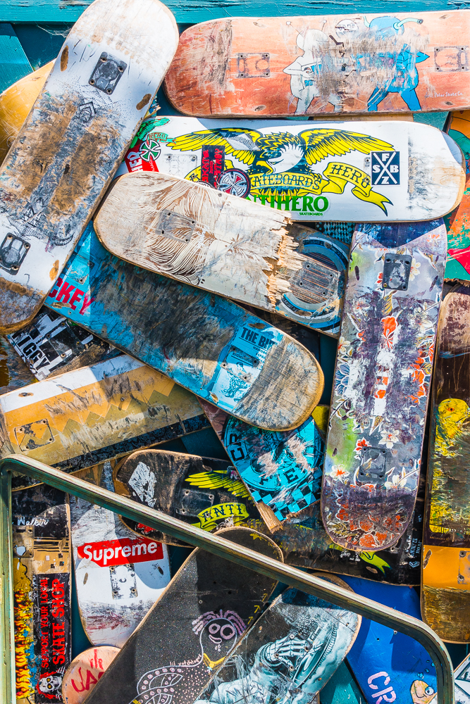 A pile of preowned skateboard decks arranged in a random fashion, some broken and some whole with each having a different design pattern in front of a skateboard shop in Santa Barbara, California.
