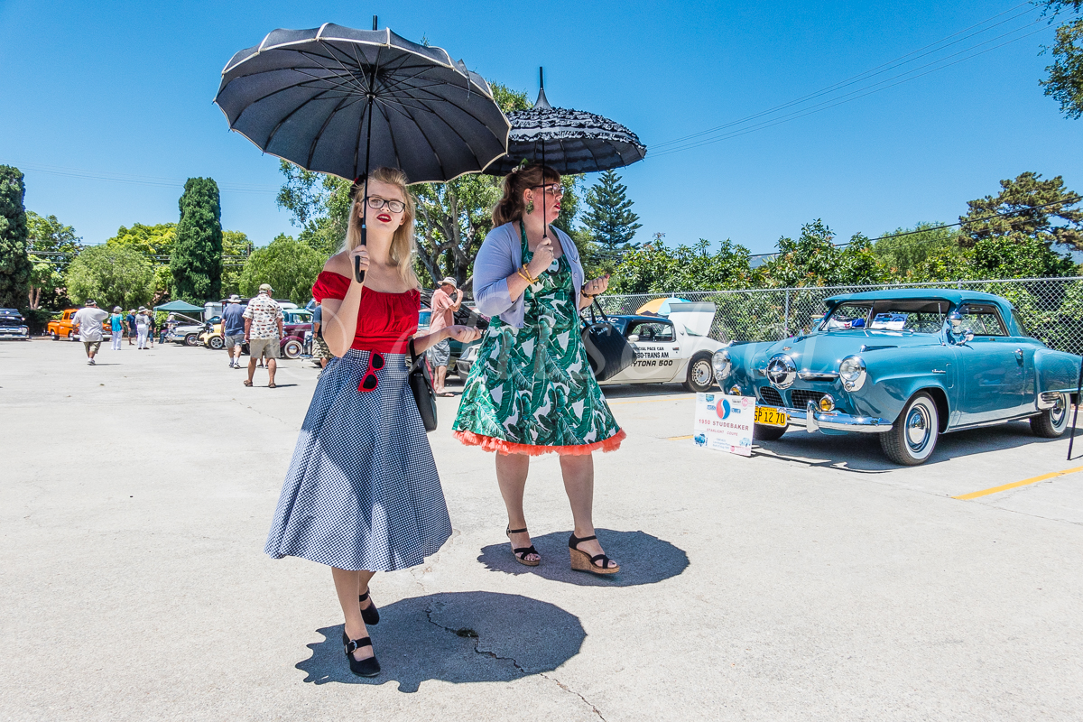 Two females in vintage clothing, walk with their parasols protecting them from the sun, at a car show in Goleta, California