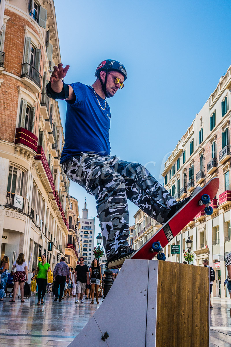 Skateboarding street performer, permanently afixed to his stand as a way to get money from passerbys in Málaga, Spain.