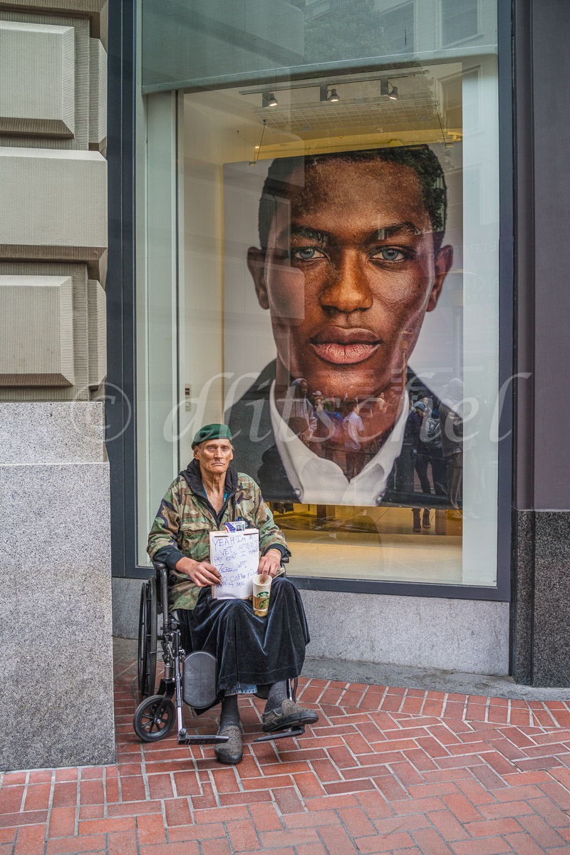A down-and-out wheelchair bound military veteran in a green beret holds a Starbucks cup begging in front of a upscale window display in San Francisco.