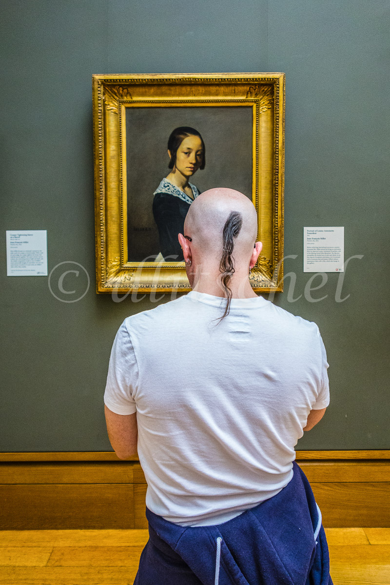 A young adult male with a shaved head and a pony tail of hair views a painting by Jean François Millet on the wall of a museum.