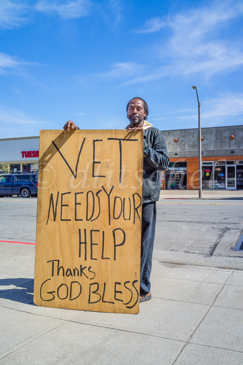 An African-American veteran of the Iraq war holds up an over-sized plywood sign outside a coffee drive through begging for money.