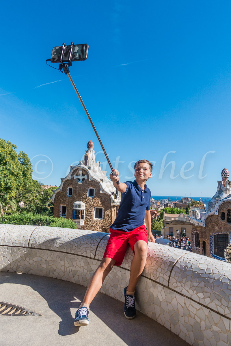 A young 11-12 year old boy takes a selfie, from an overlook of Gaudí's architecture, at Park Güell in Barcelona, Spain.