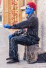 A young adult male street performer with a red wig and blue body paint on his face, neck and hands, dressed in black and sitting on his amplifier ready to perform for money in Chinatown, San Francisco, California.