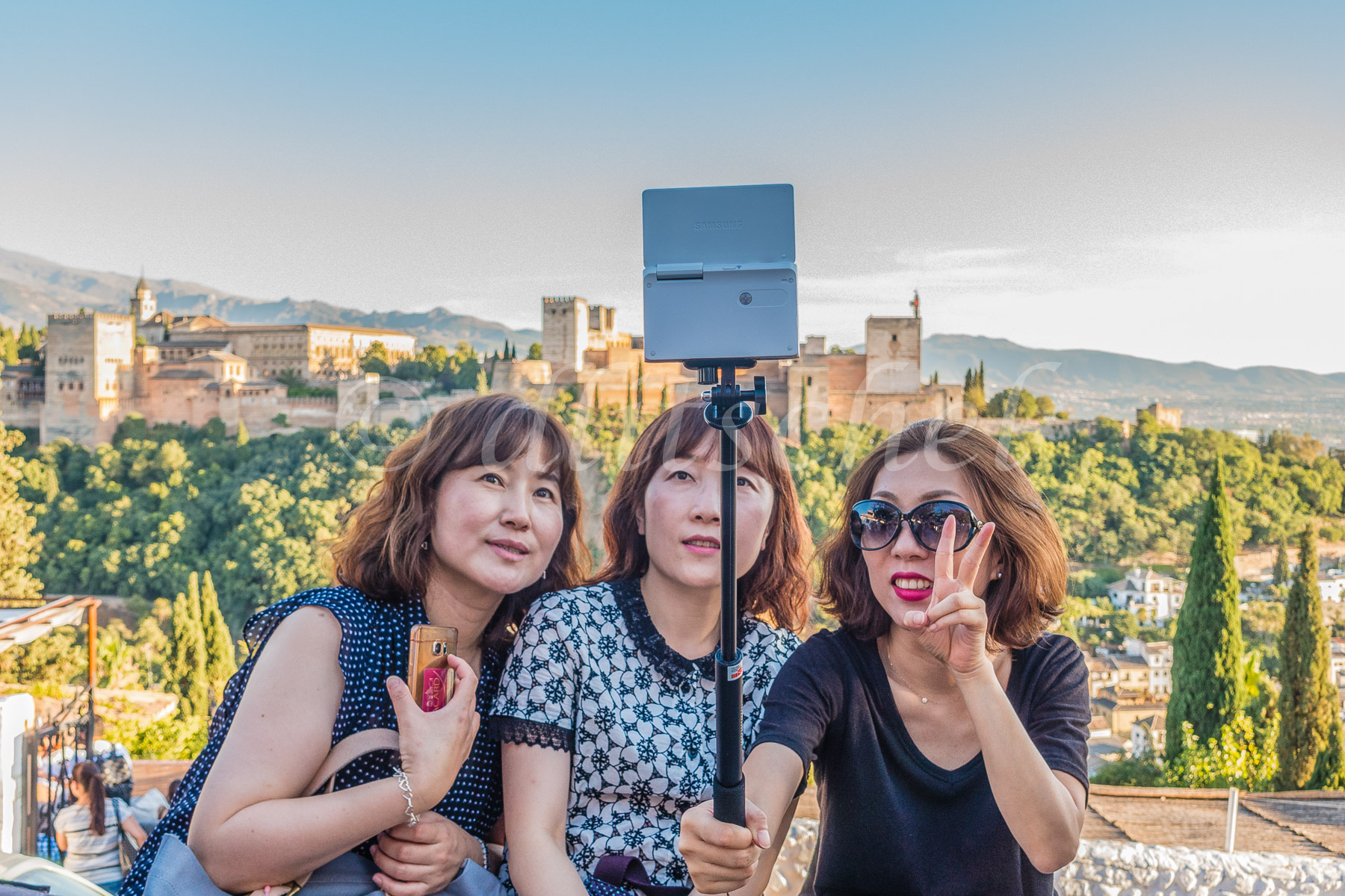 Three Asian females sit, posing together, at the Mirador San Nicolás, for a group selfie with one gesturing with the {quote}V{quote} sign with her fingers and with the Alhambra in the background in  Granada, Spain