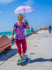 An Asian grandmother smiles as she holds a parasol and skates on her skateboard on the pier in Manhattan Beach, California.