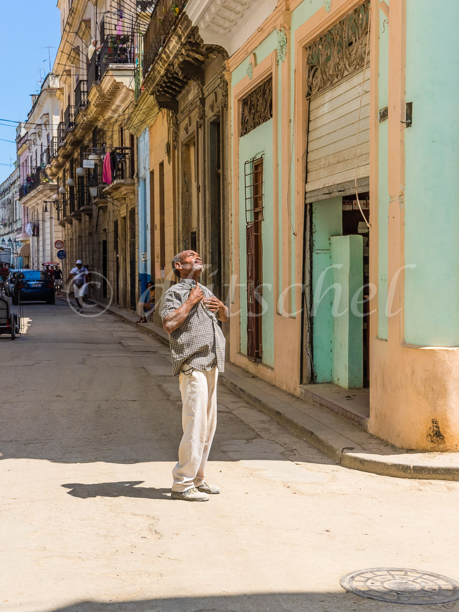 A Afro-Cuban older man stands in the middle of a Havana street in broad daylight with both of his hands on his chest having a religious experience.