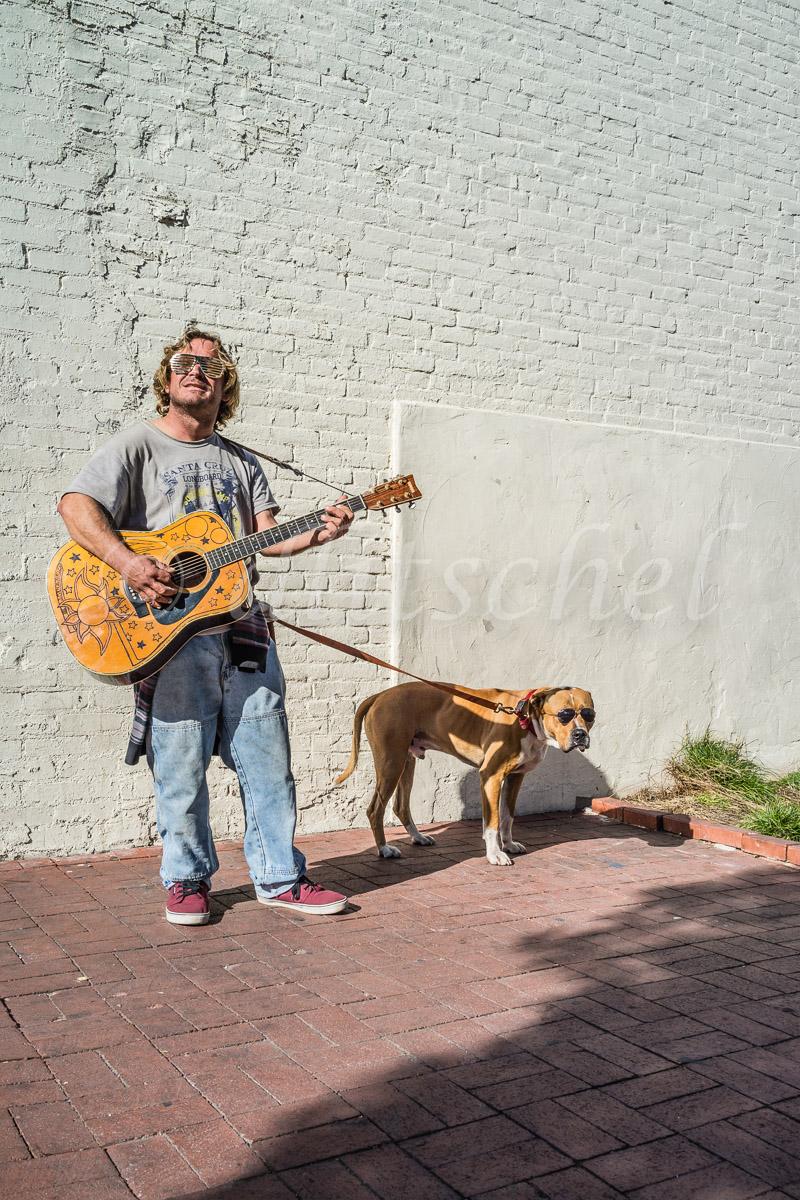 A guitar carrying man and his dog both wear sun glasses as they walk down State Street in Santa Barbara, California. A true Santa Barbara character.