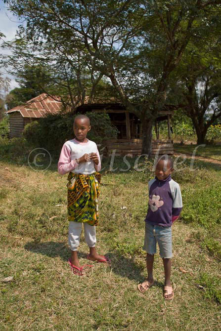 Two Tanzanian children play in the front yard of their rural house on the outskirts of Arusha, Tanzania. To purchase this image, please go to my stock agency click here.