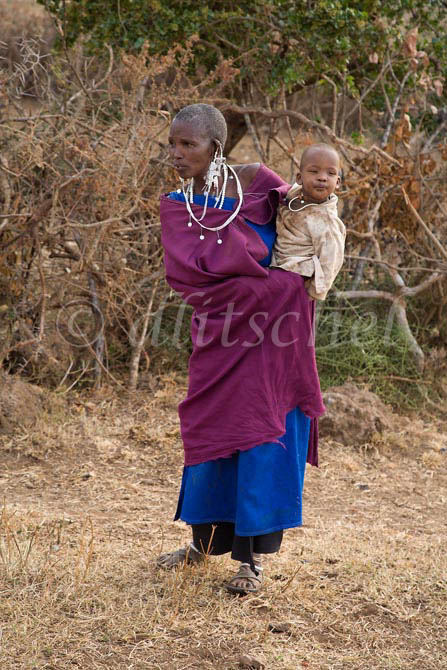 A Masai woman holds her young child on her side in a Masai village in the Sinya area of northern Tanzania. To purchase this image, please go to my stock agency click here.