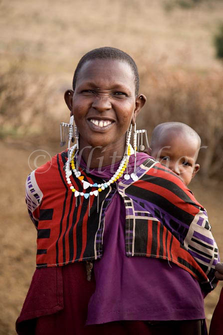 A Masai woman in traditional clothing and jewelry carries her baby on her back in a small Masai village in northern Tanzania. To purchase this image, please go to my stock agency click here.