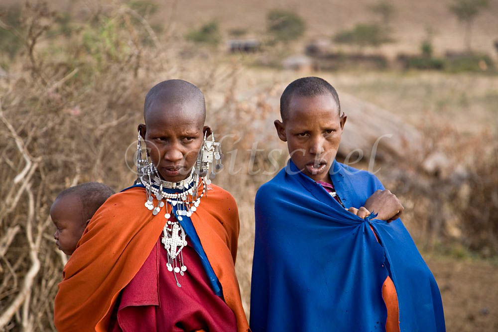 Two Masai women in traditional dress with a child in a village in the Sinya area of northern Tanzania. To purchase this image, please go to my stock agency click here.