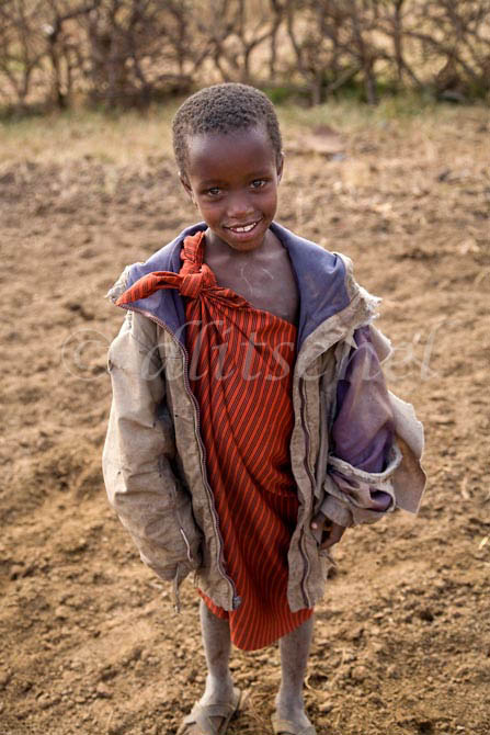 A young Masai boy wearing a tattered western style coat stands by the roadside in northern Tanzania. To purchase this image, please go to my stock agency click here.