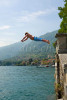 A young Italian boy dives off of a lake side wall into Lake Como in the town of Tremezzo Italy. To purchase this image, please go to my stock agency click here.