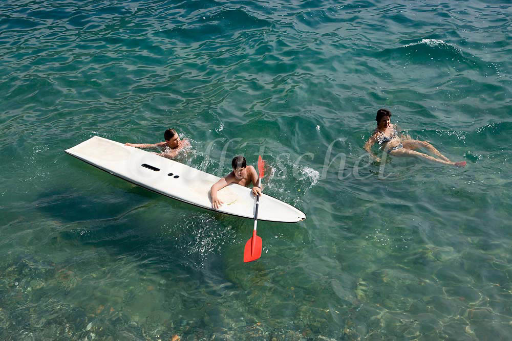 An Italian family swims with surf sail board in the waters of Lake Como at Tremezzo Italy. To purchase this image, please go to my stock agency click here.