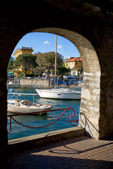 The harbor of Varenna Italy is viewed through an archway in the waterfront walkway. To purchase this image, please go to my stock agency click here.