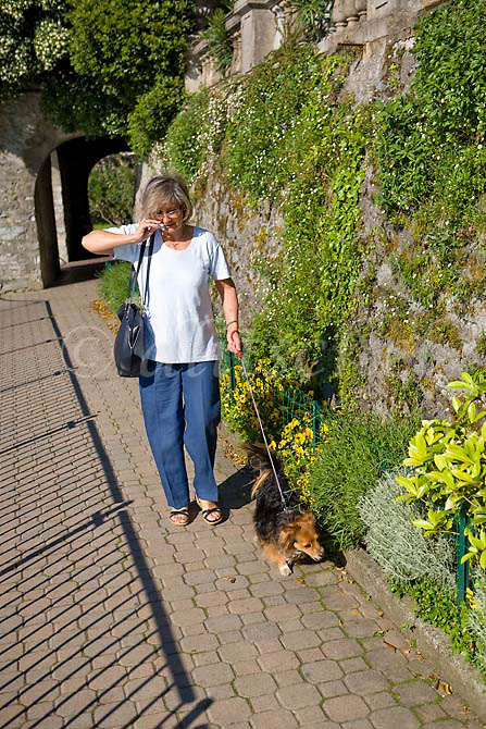 A middle aged Italian woman talks on her cell phone while walking her dog on the lakefront walkway in Varenna Italy on the shores of Lake Como. To purchase this image, please go to my stock agency click here.
