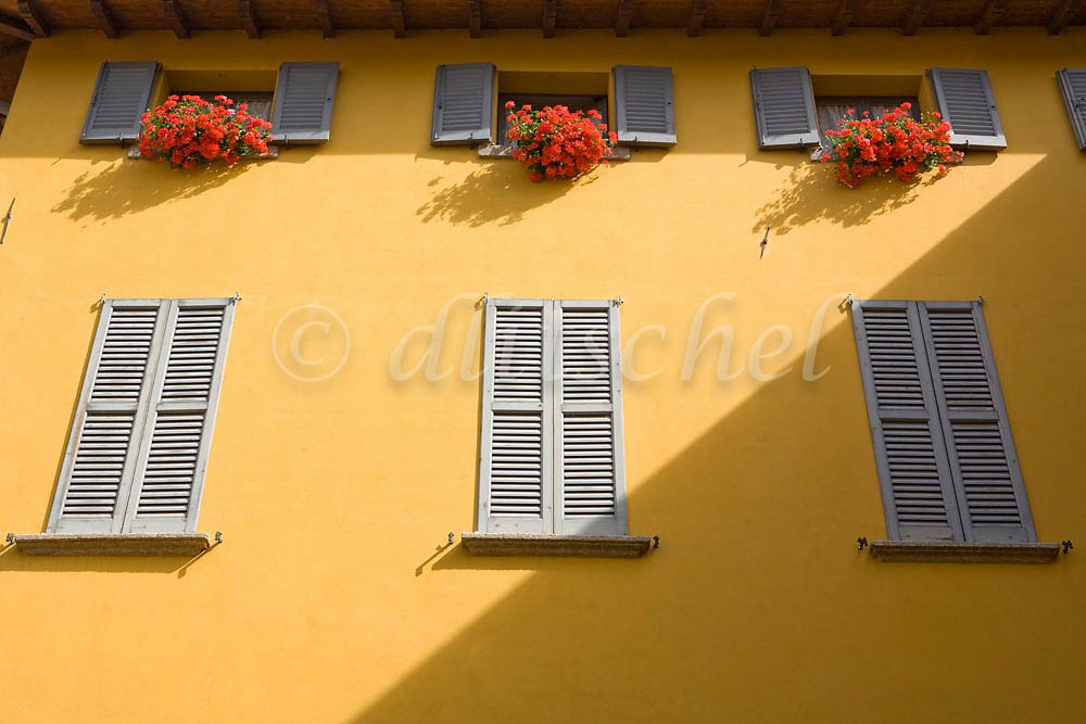Detail of the side of a building with typical shutters and flower boxes in Varenna, Italy. To purchase this image, please go to my stock agency click here.