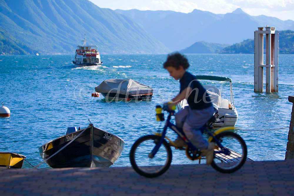 A young Italian boy rides his bicycle past the harbor overlooking beautiful Lake Como in the village of Varenna. To purchase this image, please go to my stock agency click here.