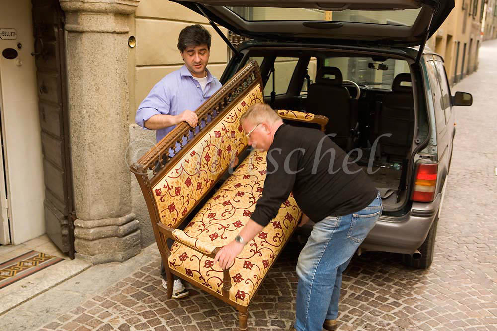 Two men move a piece of furniture in the Lake Como village of Varenna Italy. To purchase this image, please go to my stock agency click here.