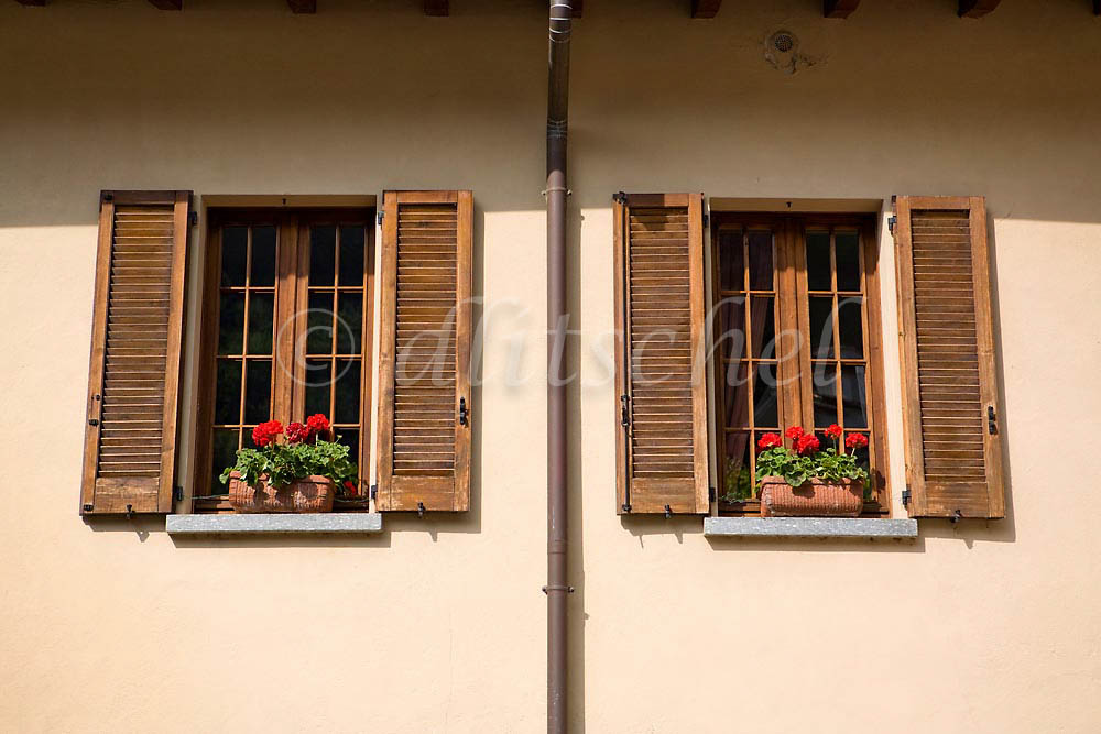 Detail of typical Italiian windows with louvered shutters and geraniums in window boxes in the Lake Como village of Varenna, Italy. To purchase this image, please go to my stock agency click here.