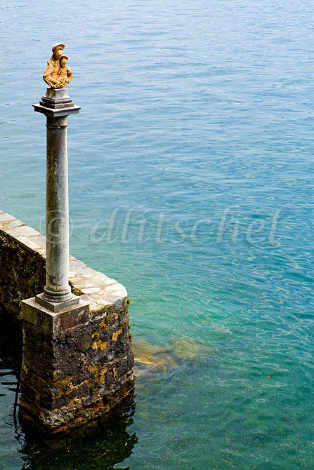 A catholic shrine of the Virgin Mary stands on top of a column at the entrance to a small harbor on Lake Como in Cernobbio Italy. To purchase this image, please go to my stock agency click here.