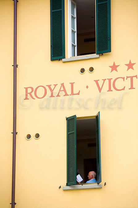 A man is seen reading in his hotel window at the Royal Victorian Hotel in the Lake Como village of Varenna Italy. To purchase this image, please go to my stock agency click here.