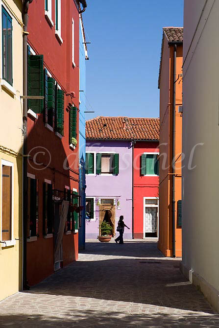 Silhouette of a woman passer by against the colorful buildings of Burano Island, Italy. To purchase this image, please go to my stock agency click here.