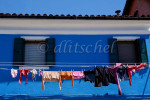 Laundry dries on a second story clothes line against a deep blue wall of a house in Burano Island, Italy. To purchase this image, please go to my stock agency click here.