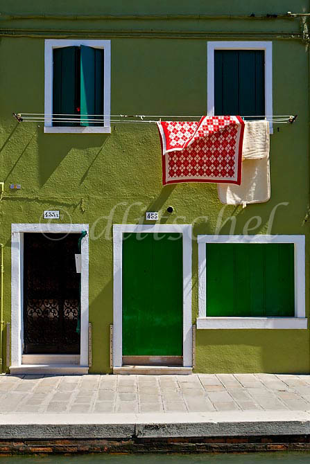 A bright red blanket hangs on a clothes line to dry against a solid green house creating a strong complimentary color relationship in Burano Island, Italy. To purchase this image, please go to my stock agency click here.