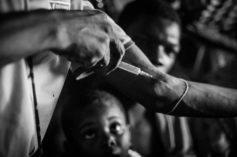The grandchild of the dealer looks up as a drug user impulsively demonstrates how to inject. The needle is from a batch donated by a local NGO needle exchange programme that distributes clean needles in exchange for used ones.